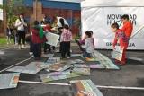 Niños y niñas se integran en la preparación del juego de gran formato previo a la Novena de Aguinaldos. Educación vial y lúdica se complementan en una actividad divertida y sana.