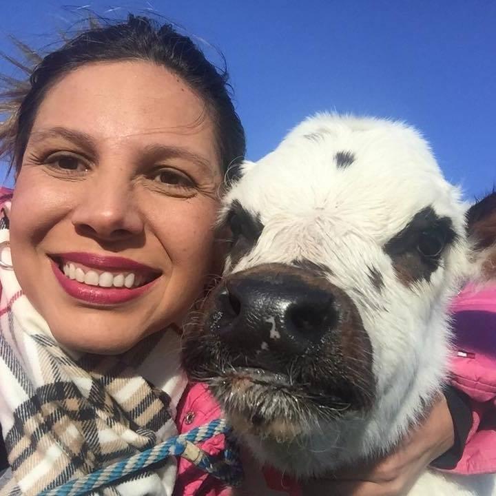 Yerly Mozo sonríe y abraza la cría de una vaca